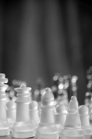 gamesmanship: glass chess pieces beautiful lit against black Stock Photo