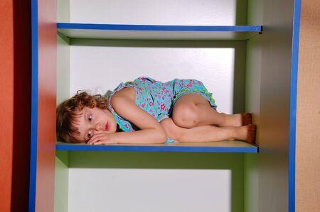 sad little girl lying on the shelf in the empty wardrobe photo