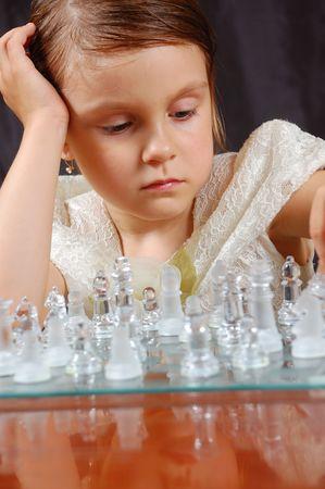 thoughtful little girl playing  glass chess photo