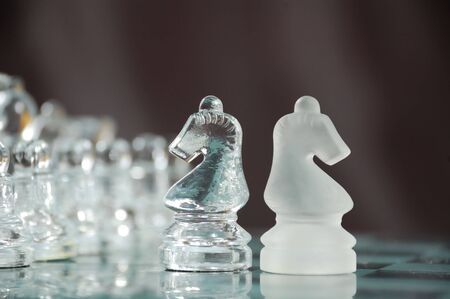 strife: two glass knights on chessboard against black background