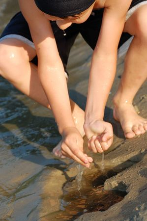 streamlet: wet boys hands trifle with water of narrow streamlet on the poachy ground