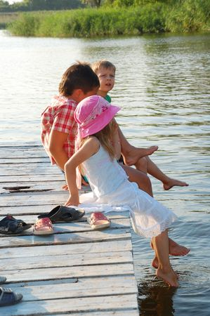 children dip their toes into the pond sitting on the gangway photo