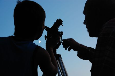 spyglass: family discovering the moon with a telescope Stock Photo