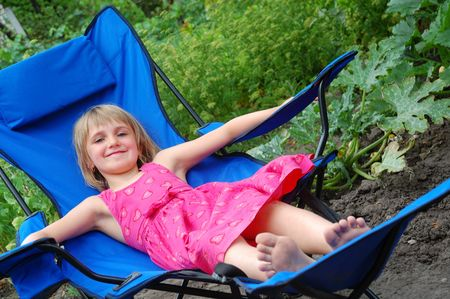 smiling barefooted girl lying in the blue lounge in the garden photo