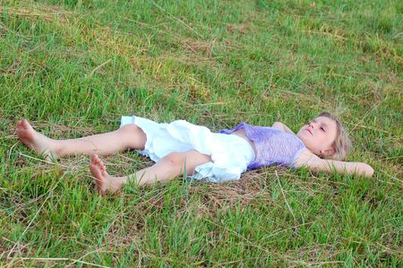 girl lies flat on the ground with hands under her head