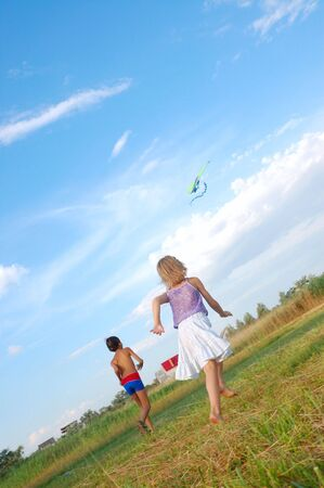 summer day children run in the meadow chasing flying kite photo