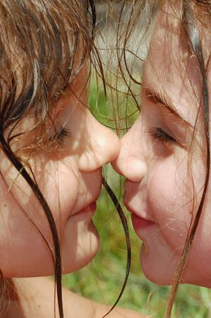 rubbing noses: two little girls with their hair wet rubbing noses