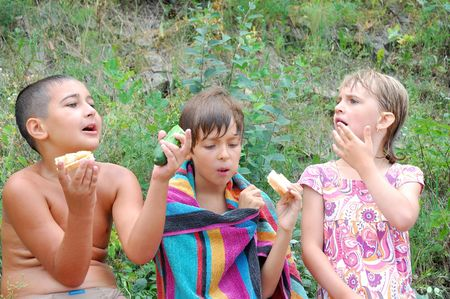 three kids having a snack after swimming photo