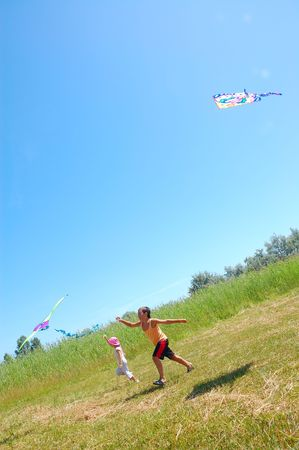 windy energy: two kids flying kites on the summer meadow