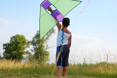 boy holding a kite up high on a sunny summer day photo