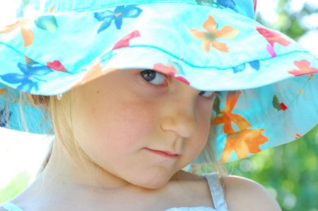 glowering: little girl wearing  a blue hat looking sullenly  Stock Photo