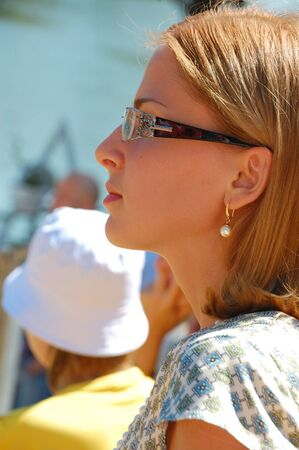profile portrait of a beautiful young woman wearing glasses outdoor on a sunny summer day photo