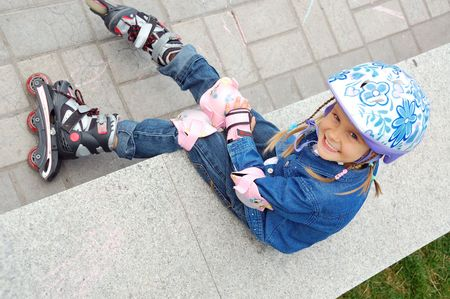 elbow pad: child with rollerskates and protective helmet and knee and elbow and palm pads