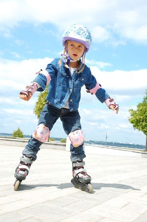 5 year old: little girl doing her first steps in rollerblading Stock Photo