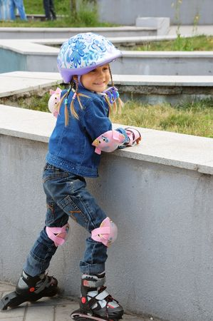 blader: youing child on in-line skates wearing the whole protective set included pads and helmet