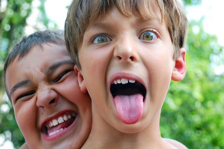 stick children: two cute boys making crazy faces outdoor