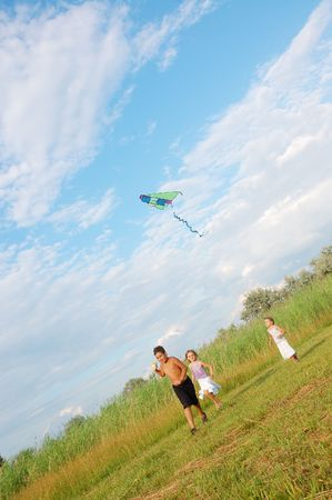 three children flying a kite in the summer meadow photo