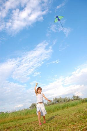flying a kite: girl running and flying a kite in the meadow Stock Photo