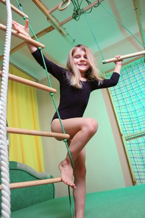 home gym: little 5 year old girl wearing a black leotard playing with her home wooden gym  Stock Photo