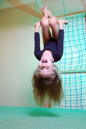 turnanzug: kleine 5-j�hriges M�dchen trug einen schwarzen Trikot spielen mit ihrem Haus aus Holz Fitnessstudio