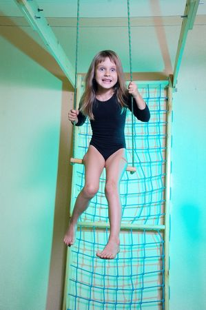 the trapeze: little 5 year old girl wearing a black leotard playing with her home wooden gym  Stock Photo