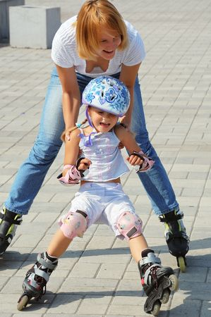 daughter and mother having fun on in-lineskates on a sunny summer day photo