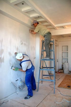 two construction workers working making indoor plastering jobs Stock Photo