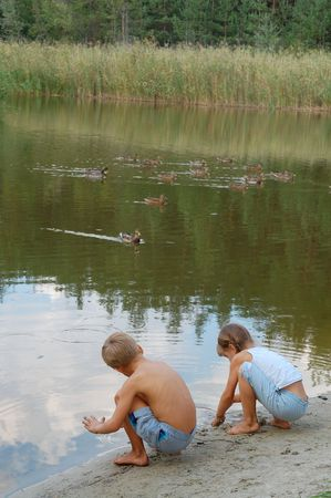 two kids playing on the lakecoast and feeding wild ducks photo
