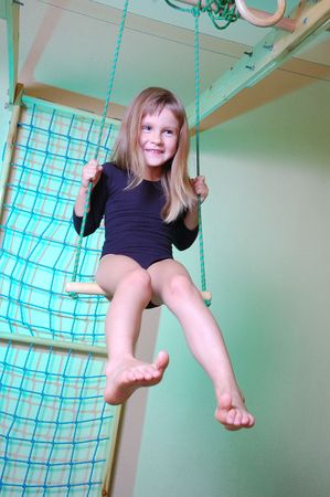 trapeze: smiling child swinging on her home gym equipment Stock Photo