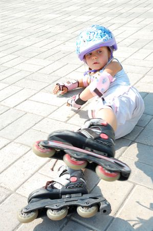 little girl with roller blades, helmet and padding set  lying down  photo