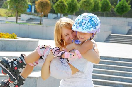 daughter and mother having fun on inline skates in the park photo