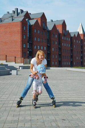 daughter and mother having fun on inline skates photo
