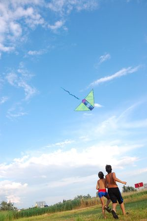 two boys flying a kite in the summer meadow photo