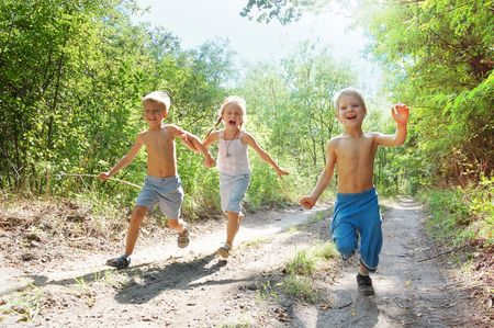 jungle girl: group of 5-6 year old happy kids running in the woods