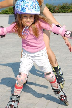 skate park: child wearing helmet and protective pads playing on inline skates with her mother