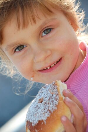 child 5 years old  eating a bun outdoor Stock Photo - 5582956