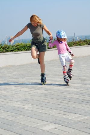 mother teaching daughter skating in the park photo