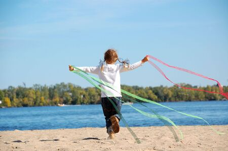 child running and playing with ribbons on the beach photo