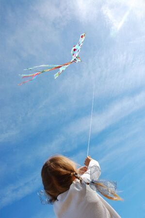 child flying a kite in the bright blue sky photo