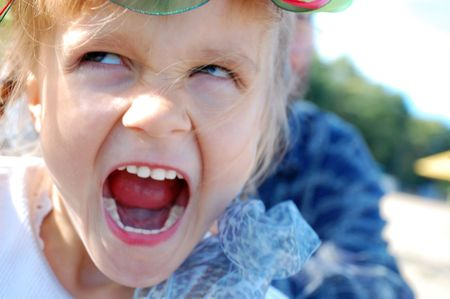 naughty child: little girl screaming and making an angry face