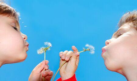 cute 4 year old girls blowing dandelion seeds awaygirls photo