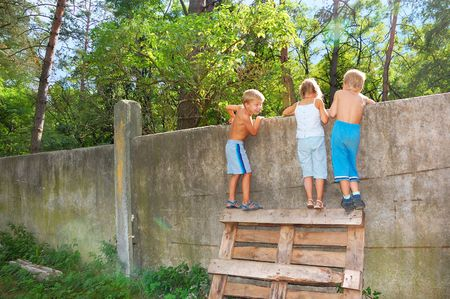 over: three 5-6 year old kids looking over the fence Stock Photo