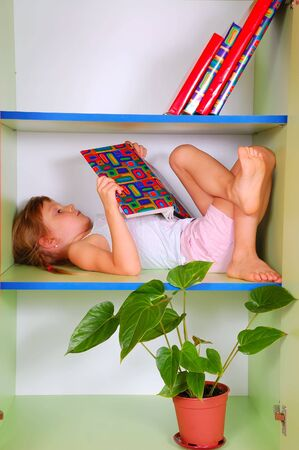 little girl lying on a bookshelf and reading a book  photo