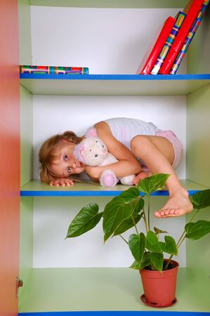 little girl lying on a bookshelf with her toy cat Stock Photo - 5671040