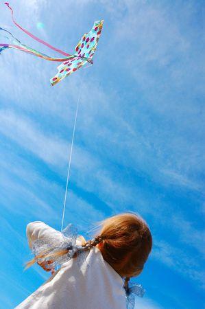 kind een vlieger in de heldere blauwe lucht ruim vliegen