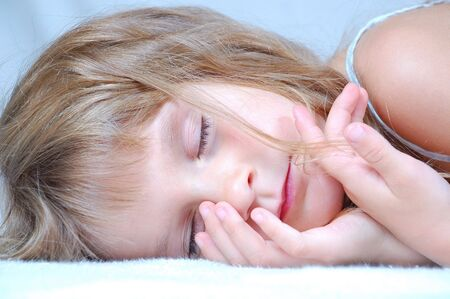 serenety: Cute caucasian little sleeping girl. Close-up composition. Stock Photo