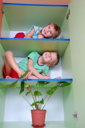 wierd: two smiling  kids with pencils on shelves playing school