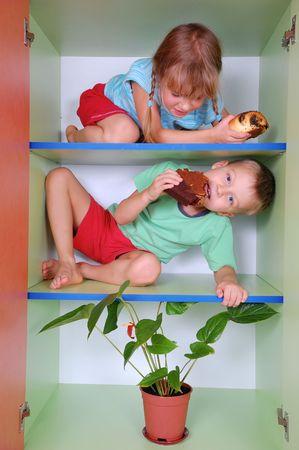 ni�os comiendo: adorables ni�os comiendo pasteles y rosquillas en los estantes de