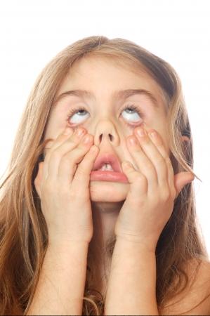 白い背景の上に怖い顔を作る小さな女の子 写真素材
