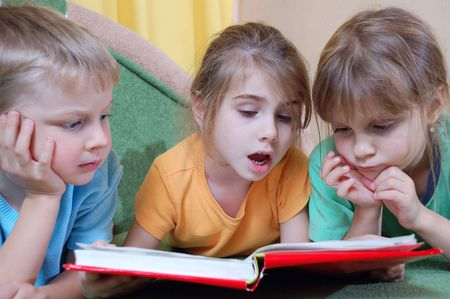 group of 5 year old kids reading their first real thick book themselves photo